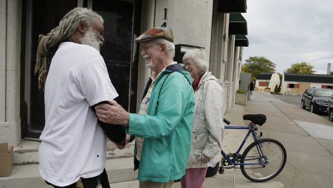 Wayne Curtis, 66, of Detroit, left, talks with Frank O'Donnell, 82, and his wife, Helen Weber, 77, both of Ferndale, during a gathering of Detroit and Grosse Pointe Park residents Sunday, Sept. 21, 2014, at a barricade on Kercheval. People at the gathering sought more unity between the neighbors.
