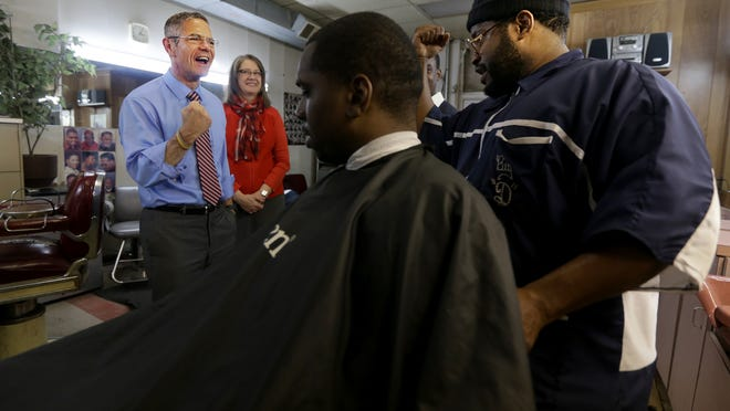 Mark Schauer, Democratic candidate for governor of Michigan, visits with Davis Ware of Detroit while he cuts James Settles III's hair at Big D's 2, a barbershop in Detroit, on Oct. 11. Schauer told prospective voters that one of his focuses will be education. In the background is his wife, Christine Schauer.