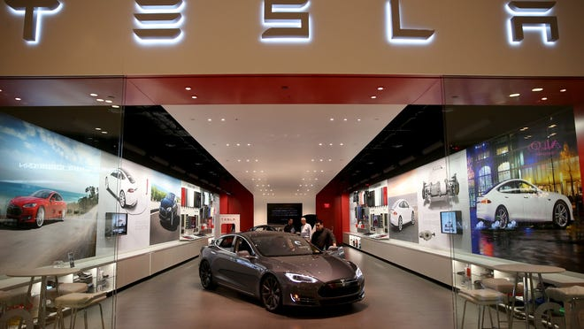 People look at a Tesla Motors vehicle on the showroom floor at the Dadeland Mall  in Miami.