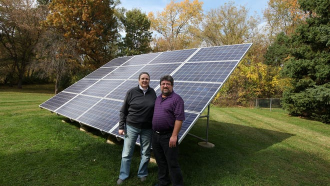 """Amy and Dave Reed, both 55, stand by their solar power panels Oct. 17, 2014, at their home in West Bloomfield. """"We went to solar power because we wanted to do our part for clean energy,"""" Amy Reed said."""