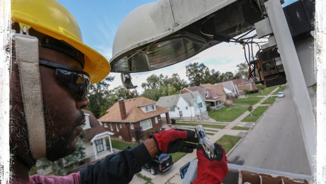 Detroit streetlight maintenance worker Leonard Robinson changes out  lights and photo cells while troubleshooting fixtures on Sussex Street on Detroit's west side on Sept. 30, 2013. The city has succeeded in replacing more than 20,000 broken streetlights this year. The LED lights being installed are twice as bright as the old lights.