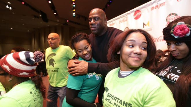 Magic Johnson greets volunteer students from Michigan State University in the sanctuary at Second Ebenezer Church in Detroit on Saturday, Nov. 22, 2014.