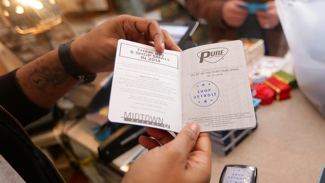 A stamp is placed in a passport after shopping at the Pure Detroit shop in the Fisher Building in Detroit on Nov. 22, 2014. To promote small business Saturday, local shops have created a passport campaign that hands out passports filled with coupons, free gifts and discounts after each stamp at participating small businesses.