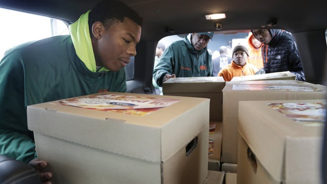 Kamar Graves, 16, left, an 11th grader of Frederick Douglass Academy in Detroit volunteers to load up food boxes with his coach Shaheed Saleem, and fellow students Da'Mon Swain, 17, and Branden Davis, 16, along with 5 other metro Detroit schools. The boxes, that will be distributed to families in need, include a turkey and trimmings as part of the UAW-Ford Holiday Box of Love Project Thursday Dec. 18, 2014. Mandi Wright/Detroit Free Press