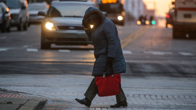 A woman shields herself from the cold wind while crossing the street at W. Fort St. and Griswold in downtown Detroit in November.