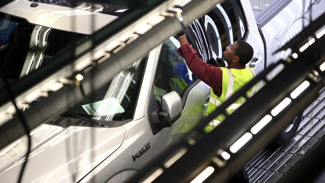 A new 2015 Ford F-150 truck goes through a quality control inspection on the assembly line at the Dearborn Truck Plant on Nov. 11. The Detroit Three automakers, whose product portfolios are still weighted more heavily toward highly profitable bigger vehicles, are expected to benefit as shoppers rush to the showroom.