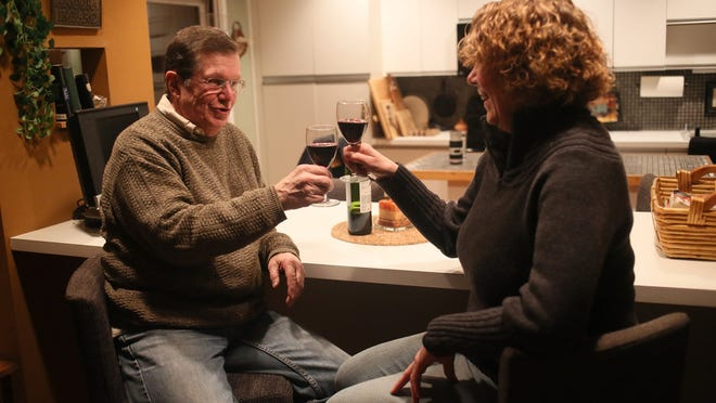 John Hoffmann and his wife, Patricia Hoffmann, both 65, of Brighton enjoy a glass of wine at home on Tuesday, Feb. 10, 2015. John had a robotic surgery procedure on his throat.