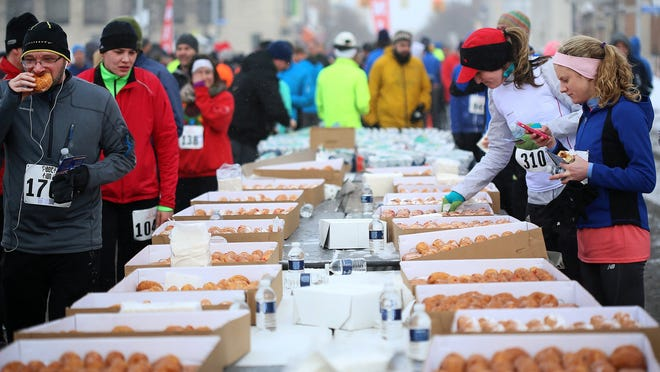 Runners walk up to a table of paczki set out for participants who finished the run.