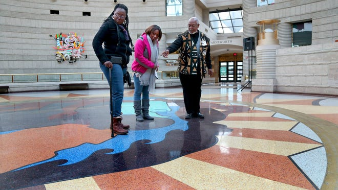 Claude Dickerson-Houilles, a Charles H. Wright Museum volunteer, explains the symbolism in the terrazzo mural by Detroit artist Hubert Massey in the circular floor to Chicago visitors last November. On Sunday, the museum will begin a months-long celebration of its 50th anniversary.