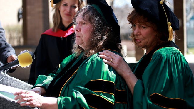 Penny Liuzzo Herrington, holds back tears, with help from her sister, Mary Liuzzo Lilleboe, after a plaque was unveiled at the Law School for her mother, Civil Rights Activist Viola Liuzzo, during the Honorary Degree ceremony for Liuzzo at Wayne State University Law School's Patriarch Auditorium in Detroit on Friday, April 10, 2015. This is the first time Wayne State University will give a posthumous doctorate degree. Luizzo, mother of five, traveled to Selma, Alabama to participate in the Voting Rights March and was shot and killed by Klu Klux Klansmen on March 25, 1965.