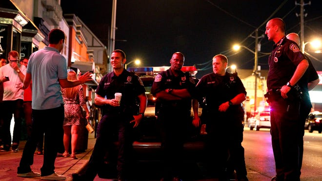 Indianapolis police officers keep watch on Broad Ripple revelers during the wee hours of July 12, 2014, part of a move to curb violence.