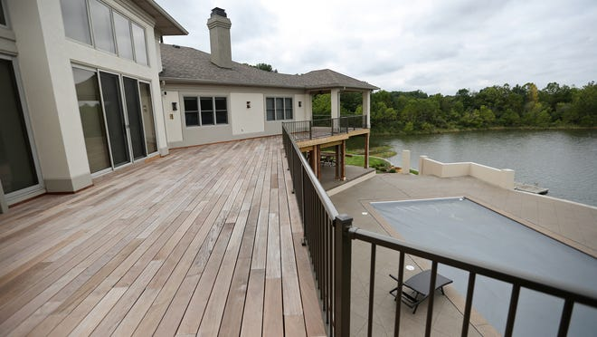 A new deck lines the back of the home.The lower level outside includes a pool, and down below Fox Lake.