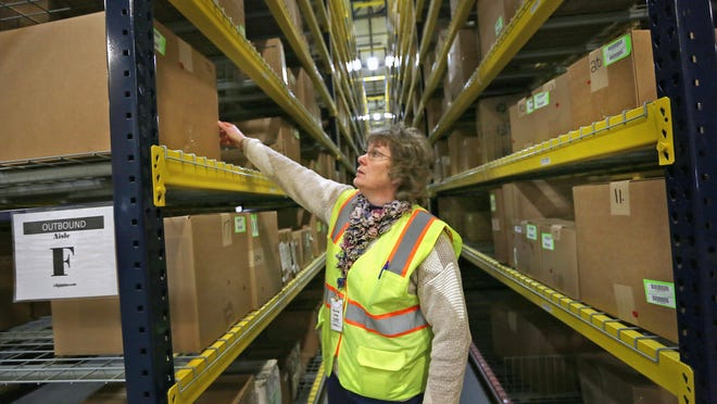 General manager Karen Ling shows how boxes are stowed at Liquidity Services Inc. in Plainfield. The boxes are full of items that will be resold.