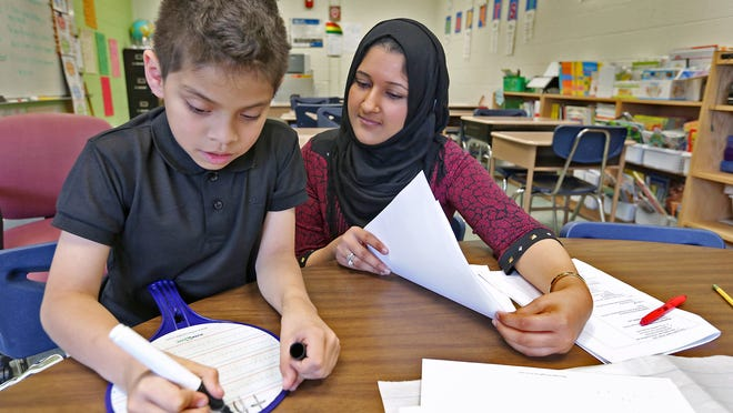 """Mariam Khan teaches English to kids from around the world, such as new student Joshua Miranda, at Indianapolis Public School 79. """"My hardest group is first-graders,"""" Khan said. """"They speak so many languages and no English. Getting used to the environment is hard for them."""""""