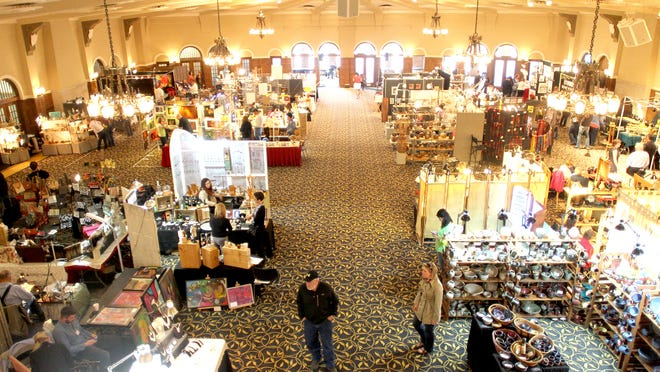 Patrons file through numerous art and craft displays Sunday at the Riverbank Art Fair in the Iowa Memorial Union Main Lounge in Iowa City.