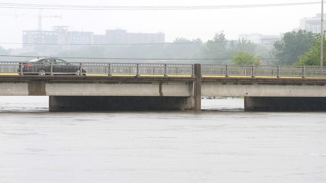 A driver stops on the Park Road bridge to take a photo of the flooded Iowa River on Saturday.