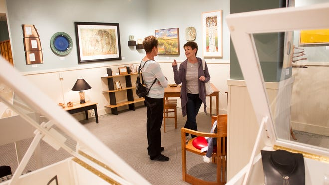 "Dana McMahon of Iowa City, right, chats with Luanne Alleman of Corona, Calif., on Wednesday at the Iowa Artisans Gallery. The gallery, which concentrates on contemporary American craft, has organized a ""30 Years of Art & Artists"" exhibit."
