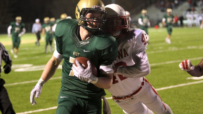 West High's Tyler Eads gets pushed out of bounds by Ottumwa's Matthew Moreland during their Class 4A first round playoff game on Wednesday, Oct. 29, 2014.  David Scrivner / Iowa City Press-Citizen