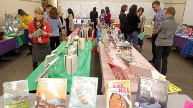 "Teachers and librarians browse book selections during the Iowa City Community School District's ""Bookapalooza"" on Thursday."