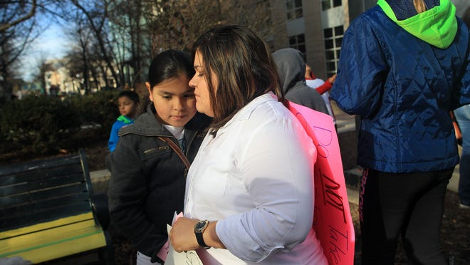 Gloria Villatoro consoles her 10-year-old daughter, Angela, following a rally in support of her husband, Max Villatoro, on the pedestrian mall in Iowa City on Tuesday.