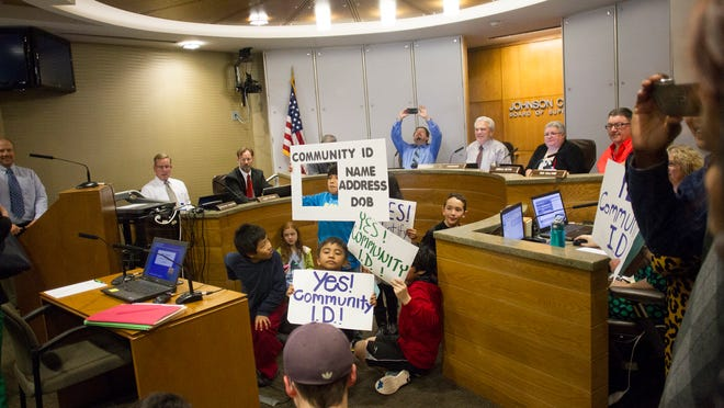 Community ID supporters show off their signs at the beginning of the Johnson County Board of Supervisors meeting Thursday at the Johnson County Administration Building. The board unanimously approved the creation of a community ID program to help residents obtain identification even if they lack certain documentation.