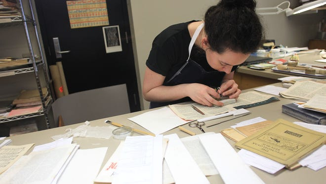 University of Iowa student technician Katie Rouw repairs a damaged book at the Conservation Lab inside the University of Iowa Main Library on April 14, 2015. The process, known as mending, uses Japanese tissue to patch cuts in the paper.