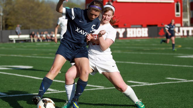 City High's Shelby Burden fights off Cedar Rapids Xavier's McKenna Lloyd during their game on Thursday.