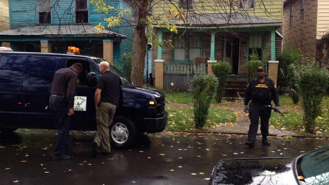 Police confer outside the house where the dogs lived that attacked an unidentified man Thursday on Detroit's east side.