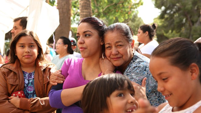 Family members comfort one another during the Dia de los Muertos celebration held at Desert Memorial Park in Cathedral City on Saturday.