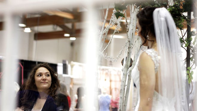 Regina Lemon, of Salem, looks at model Amber Shewbert as she wears a gown from Bridal Gallery during the Oregon Wedding Showcase at the Oregon State Fairgrounds in Salem on Saturday, Jan. 24, 2015.