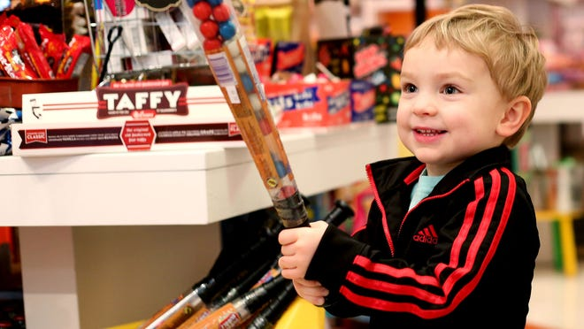 Evan Good, 3, of Salem, plays with a candy-filled baseball bat at Ricky's Bubbles & Sweets Shoppe in downtown Salem.