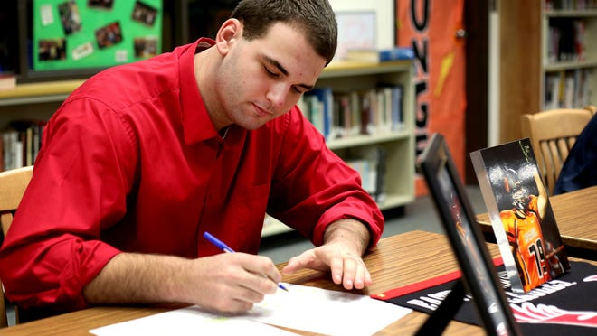 Levi Long signs a letter of intent to play football with Eastern Washington University during the 2015 National Signing Day ceremony at Sprague High School in Salem on Wednesday, Feb. 4, 2015.