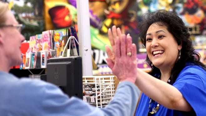 """Sales team member Angie Miller (right) high-fives customer Kim Koopman, of Salem, for choosing to donate $5 to the Special Olympics at the Toys """"R"""" Us location on Lancaster Drive NE in Salem on Tuesday, Feb. 24, 2015. The Salem location is one of the top collectors in a national fundraising campaign by Toys """"R"""" Us to raise money for the Special Olympics."""