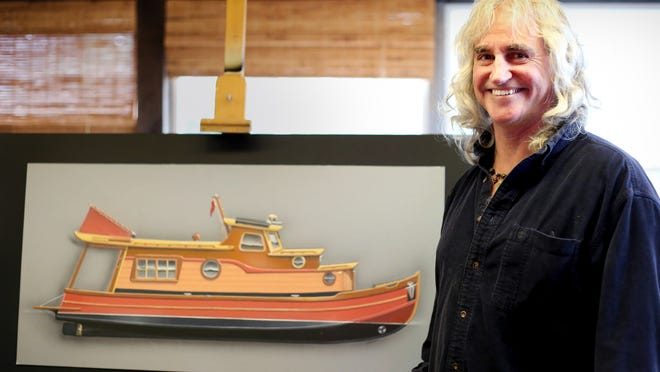 Kerry Elwood, a Salem airbrush artist, stands next to a rendering of the hand-crafted wooden houseboat that he's been commissioned to build.