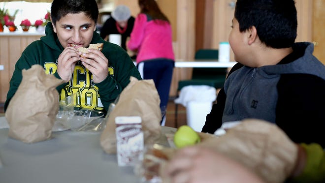 Janderi Perez Alejandre (left), 12, and his neighbor Jose Salazar, 11, eat turkey and cheese sandwiches during the Spring Break Lunch program put on by the Marion-Polk Food Share at the Oak Park Community Bible Church in Salem on Monday, March 23, 2015.