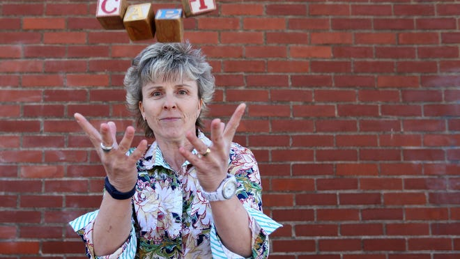 Statesman Journal columnist Capi Lynn will test her hand-eye coordination when she attempts to learn how to juggle. Her current skill level, using wooden blocks from her desk that spell her first name, is captured during a photo shoot on Monday.
