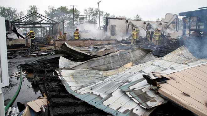 Firefighters inspect the burned wreckage of the Green Dragon farmer's market in Ephrata, Pennsylvania, Saturday. According to LancasterOnline.com, the famous Lancaster County farmer's market was damaged by a two-alarm fire Saturday morning.