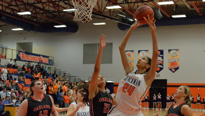 Blackman's Jazz Bond (24) goes up for a shot over Maddie Cook during the Lady Blaze's 57-42 win over Oakland on Tuesday night.
