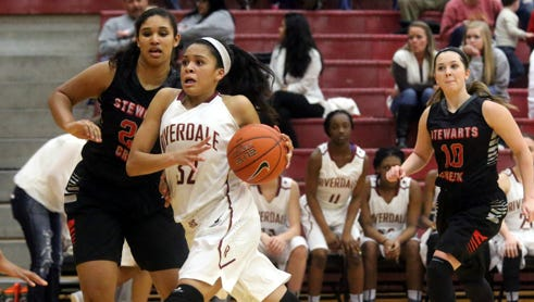 Riverdale's Brinae Alexander pushes toward the basket around Stewarts Creek's Ryann Carpenter and goes up for a shot during the Tuesday Jan. 6, 2015 game at Riverdale. Stewarts Creek's Erica Jones comes up from behind.