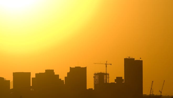 The sun sinks behind the downtown Phoenix skyline, a moment city residents await when the temperatures soar.
