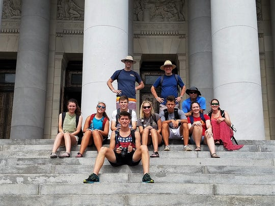 A group of seven teens and four adults from Christ Community Church in Montreat, sit on the steps of the capital building in Havana, Cuba during a 10-day mission trip to the country in July.