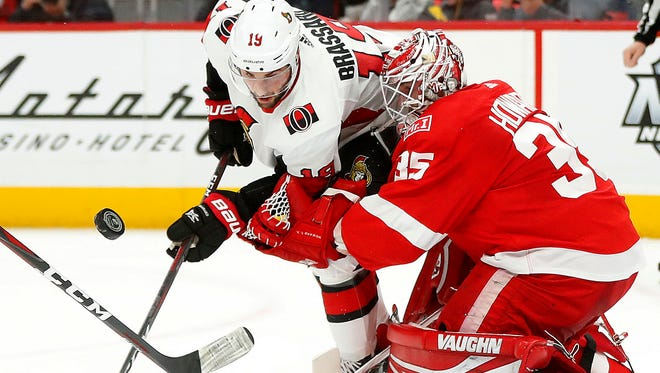 Wings goaltender Jimmy Howard stops a shot by Senators center Derick Brassard during the first period Wednesday in Detroit. Howard made 33 saves in the 2-1 OT win.