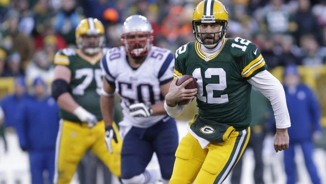 Green Bay Packers quarterback Aaron Rodgers runs for a first down in the first quarter of Sunday's game against New England at Lambeau Field.