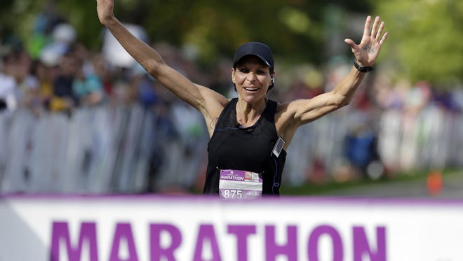 Sara Kontos Weitz of Menasha crosses the finish line as the top female finisher in the Community First Fox Cities Marathon at Riverside Park in Neenah, Wis., Sunday, September 20, 2015. Ron Page/Post-Crescent Media