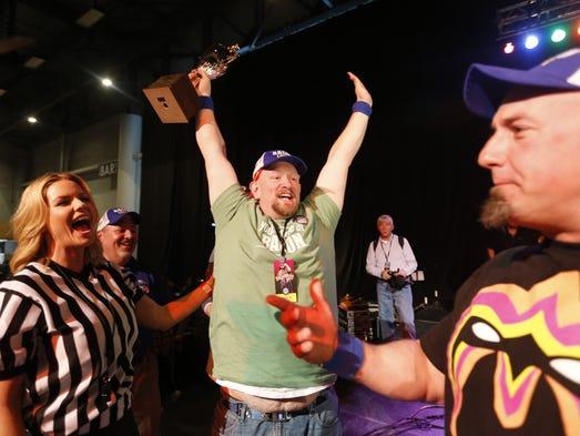 Kevin Graham of Des Moines holds up the trophy after