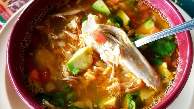 Guatemax's chicken stew was broth made with tomatillos, large shreds of chicken, peas, red peppers, carrots, onion, avocado chunks, rice, and cilantro.