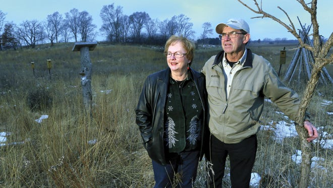 In this photo taken on Dec. 14, 2014, Marti and Ron Martin stand on the winter-time prairie that they created around their home in rural Milton, Wis..  More than 20 years ago, the Martins turned a love of nature into one of the area's first land restoration businesses.