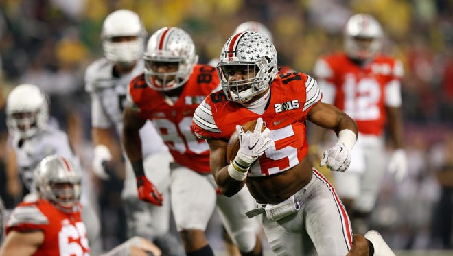Ohio State Buckeyes running back Ezekiel Elliott (15) runs against the Oregon Ducks in the first quarter  in the 2015 CFP National Championship Game at AT&T Stadium.