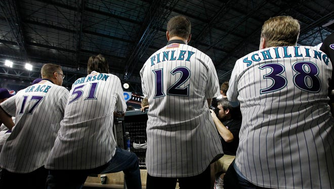 Curt Schilling, Steve Finley, Randy Johnson, and Mark Grace watch the highlights of Game 7 of the World Series during reunion ceremonies of the 2001 World Series champion team at Chase Field in Phoenix.