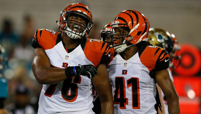 Bengals defensive end Ryan Brown (left) celebrates with defensive back Floyd Raven after making a tackle for a loss in the fourth quarter of Sunday's loss to the Jacksonville Jaguars. Raven was one of 11 players cut on Monday.